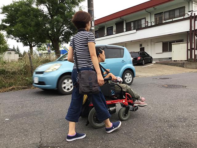 利用者が介助者と共に道を歩いている